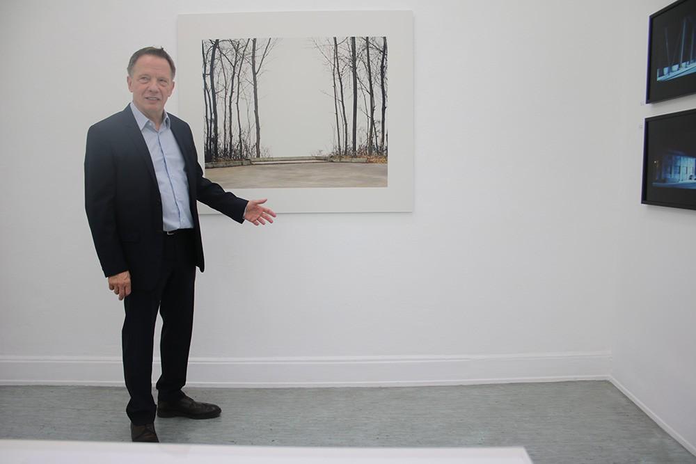 Der Galerist Lothar Albrecht vor einer Fotografie von Oliver Bloberg