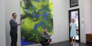 """Foto: privat (v.l.) Ralf Seinecke, Daniel Schierke und Edda Rössler. Im Hintergrund das Gemälde """"Breaking Blue"""" von Laura Aberham."""