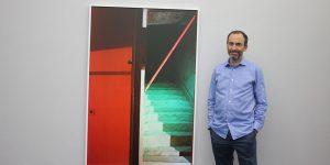 Galerist Daniel Schierke vor einer Fotografie von Andrea Grützner